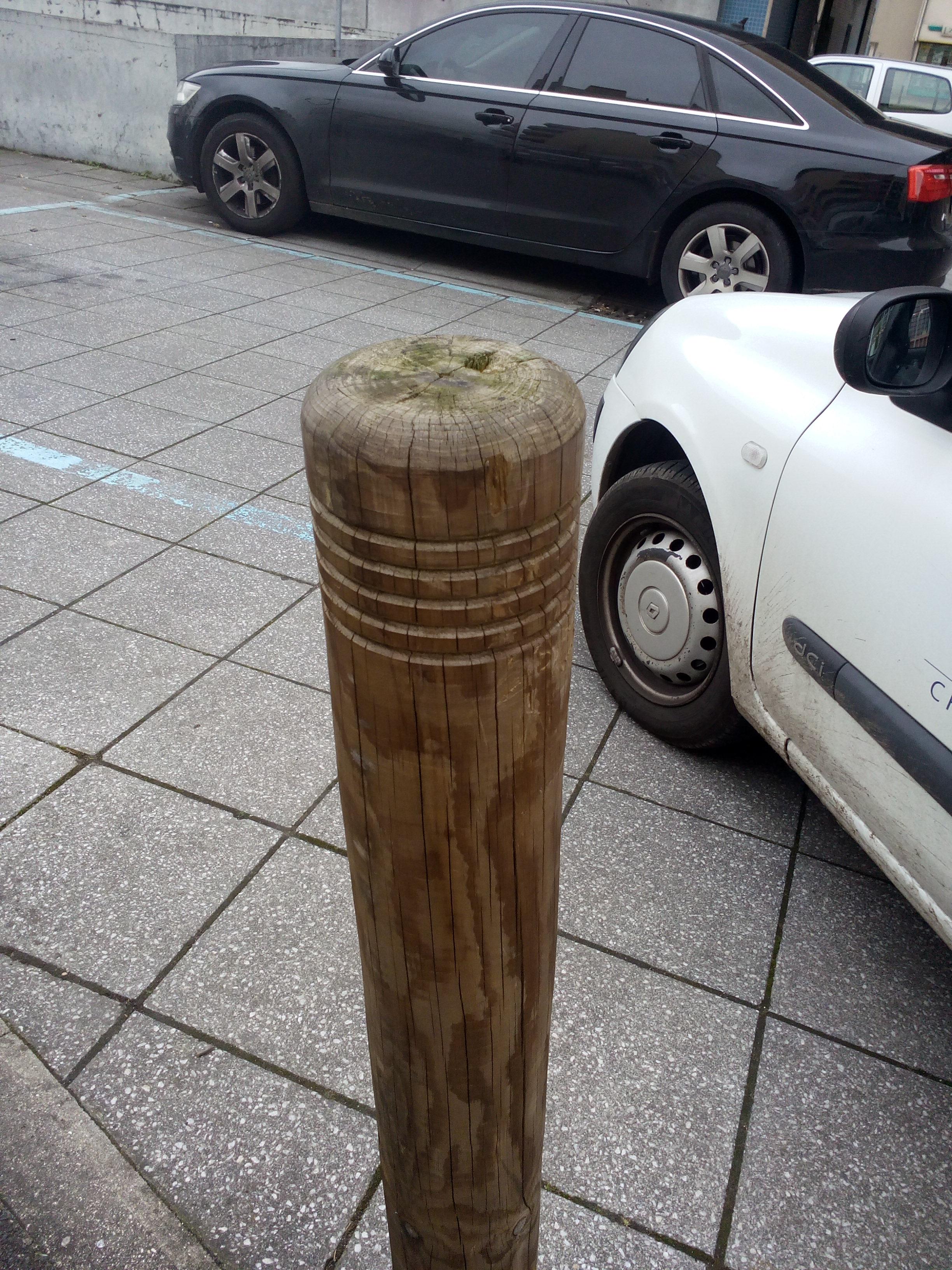 Rondin de bois utilisé en ville pour restreindre le stationnement